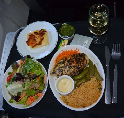 Grilled chicken with rice, green beans, and salad aboard American Airlines.
