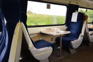 Two seats facing table aboard East Coast Line train to Edinburgh, Scotland.